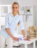 Portrait of female architect with blueprints at desk in office, isolated — Stock Photo