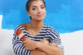 Portrait of female painter sitting on floor near wall after painting. — Stock Photo