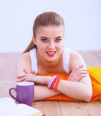 Smiling young woman lying on a white floor with pillow — Stock Photo