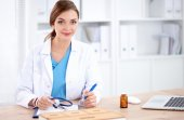 Beautiful young smiling female doctor sitting at the desk and writing. — Stock Photo