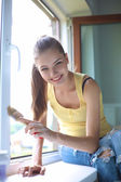 Woman with a paintbrush carefully finishing off around a window frame — Stock Photo