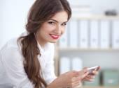 Επιχειρηματίας στέλνει μήνυμα με το smartphone που κάθεται στο γραφείο — Φωτογραφία Αρχείου