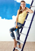 Happy beautiful young woman doing wall painting, standing near ladder — Stock Photo