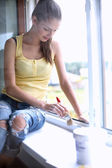 Woman painting wall of an apartment with a paintbrush carefully finishing off around  window frame — Stock Photo