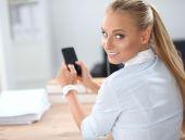 Wysyłanie wiadomości z smartphone siedząc w biurze interesu — Zdjęcie stockowe