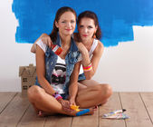 Two beautiful young woman doing wall painting, sitting — Stock Photo