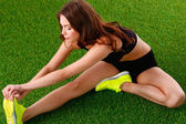 Woman doing stretching exercises on the green grass — Stock Photo