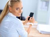 Podnikatelka odesílání zpráv s smartphone sedět v kanceláři — Stock fotografie