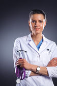 Young doctor woman with stethoscope isolated on grey  — Стоковое фото