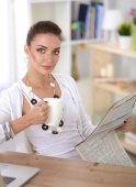 Sexy geschäftsfrau holding Zeitung sitzen an ihrem Schreibtisch im Büro — Stockfoto