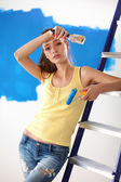 Beautiful young woman doing wall painting, standing near ladder — Stock Photo