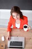 Attractive woman sitting at desk in office, working with laptop computer — Stock Photo