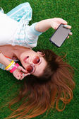 Beautiful young woman making selfie by her phone while lying in green grass — Stock Photo