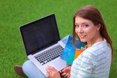Mujer joven con portátil sentado en la hierba verde — Foto de Stock