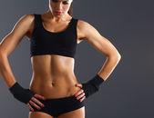 Mięśni młoda kobieta stojąc na szarym tle — Zdjęcie stockowe