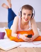 Ung kvinna liggande på golvet och lyssnar på musik — Stockfoto