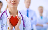 Female doctor with stethoscope holding heart — Stock Photo