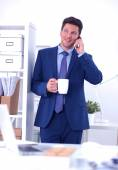 Smiling businessman standing and using mobile phone in office — Stock Photo