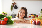 Young woman standing near desk in the kitchen — Stock Photo