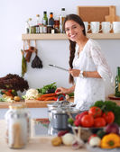 Young woman using a tablet computer to cook in her kitchen — Stock Photo