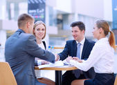 Group of happy young business people in a meeting at office — Stock Photo