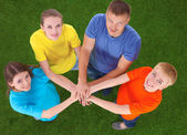 People joining their hands  on green grass — Stock Photo