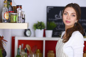 Young woman standing in kitchen at home — Stock Photo