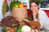 Young woman reading cookbook in the kitchen, looking for recipe — Stock Photo
