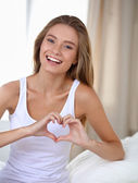 Beautiful woman showing heart shape on her hand , sitting bed — Stock Photo