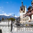 Spring view of Peles Castle with snowy Bucegi Mountains in the background. — Stock Photo #72826993