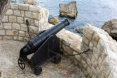 Old iron cannon pointing out to sea defending a castle — Stock Photo