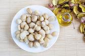 Zátiší s pohled shora Macadamia ořechy v desce a láhev oleje — Stock fotografie