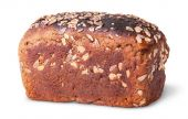 Unleavened black bread with nuts seeds and dried fruit rotated — Stock Photo