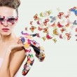 Beauty woman wearing sunglasses and holding shoes — Stock Photo #61237441