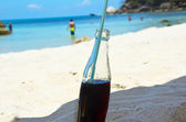 Bottle of brown soda on the beach — Stock Photo