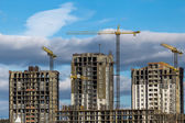 Construction of high-rise buildings with cranes — Stock Photo