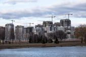 Construction of high-rise buildings with cranes on river bank — Stock Photo