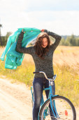 Beautiful brunette girl at cycling on dirt road — Foto Stock
