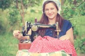 Young seamstress with vintage hand sewing machine — Stock Photo