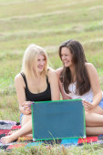 Laughing student girls holding board for writing — Stock Photo