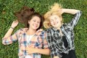 Blonde and brunette girl lying on grass — Stock Photo