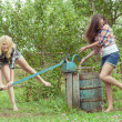 Blonde and brunette soaking each other with water — Stock Photo #59275557