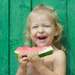 Two-year-girl laughing and holding watermelon — Stock Photo #62376241
