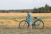 Teenager boy holding bicycle in farm field — Foto Stock