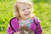 Little girl laughing during holding nest with eggs — Stock Photo