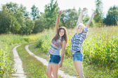 Friends dancing on country road — Stock Photo