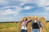 Friends having sunbathe on large round bale — Stock Photo
