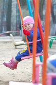 Little girl sitting on playgrounds swing — Stock fotografie