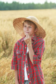 Portrait of teenage farm boy in wide-brimmed hat and oat cereal ears straw — Stock Photo