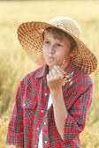 Portrait of teenage farm boy in wide-brimmed hat chewing oat cereal ears straw — Stock Photo